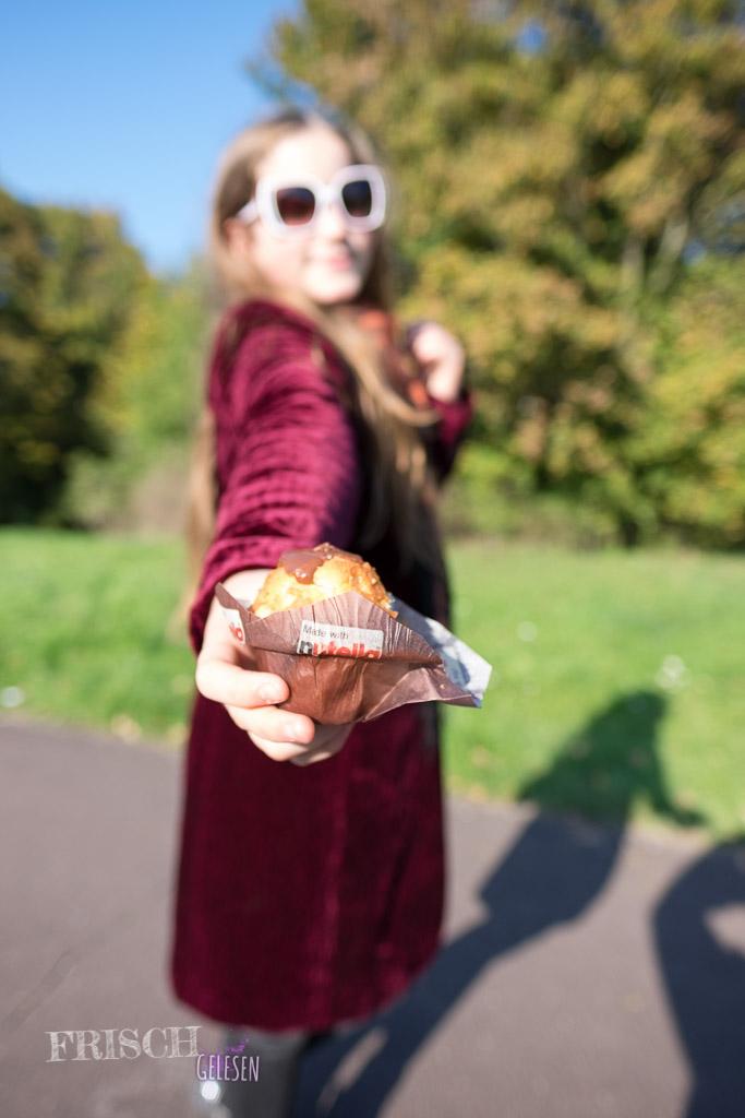 Mädchen hält Nutella Muffin in die Kamera